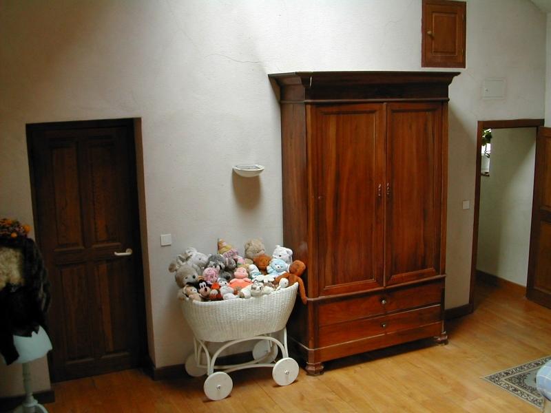 Armoire haute au fond pour ranger vos affaires et berceau décoratif débordant de peluches. A gauche accès à la salle de bans des enfants.