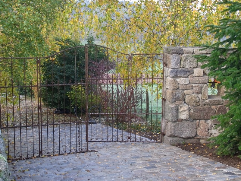 L'allée de pavés et le portail en fer forgé ancien
