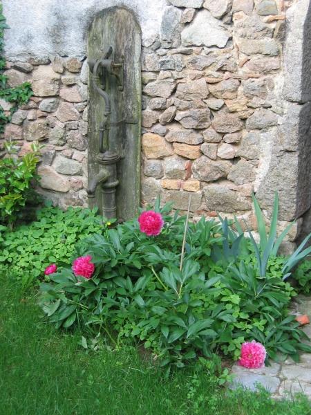 Une vieille pompe sur un mur d'enceinte ven pierre dans la cour
