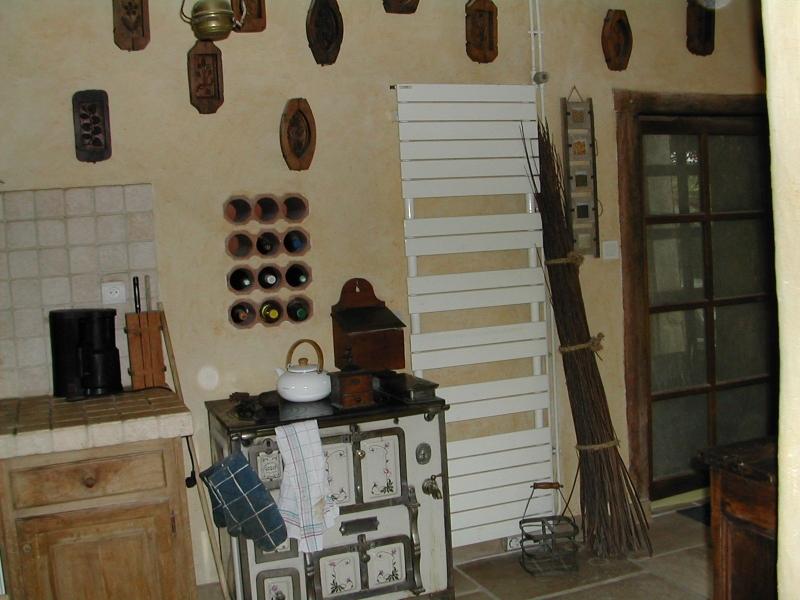 La cuisine de ma maison de campagne, Vieux fourneau blanc émaillé, range bouteille niché dans le mur et vieux moules à beurre au mur.