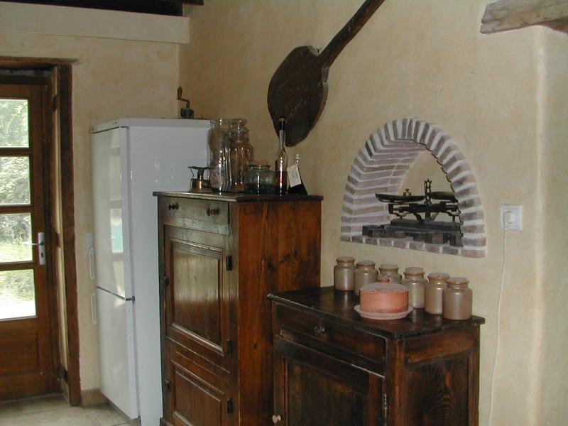 La cuisine de ma maison de campagne - Niche décorative avec sa vieille balance, placard de rangement et combiné frigidaire congélateur au fond.