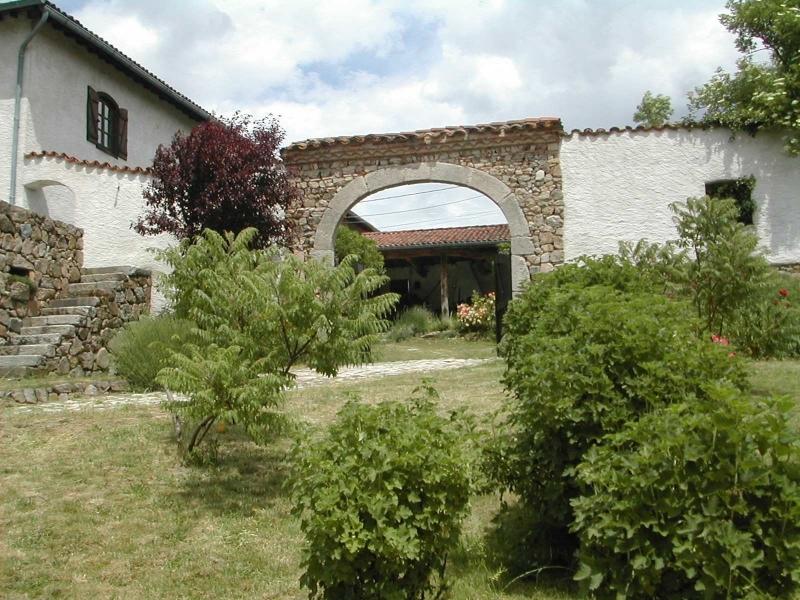 Maison et porche en pierre vus du jardin
