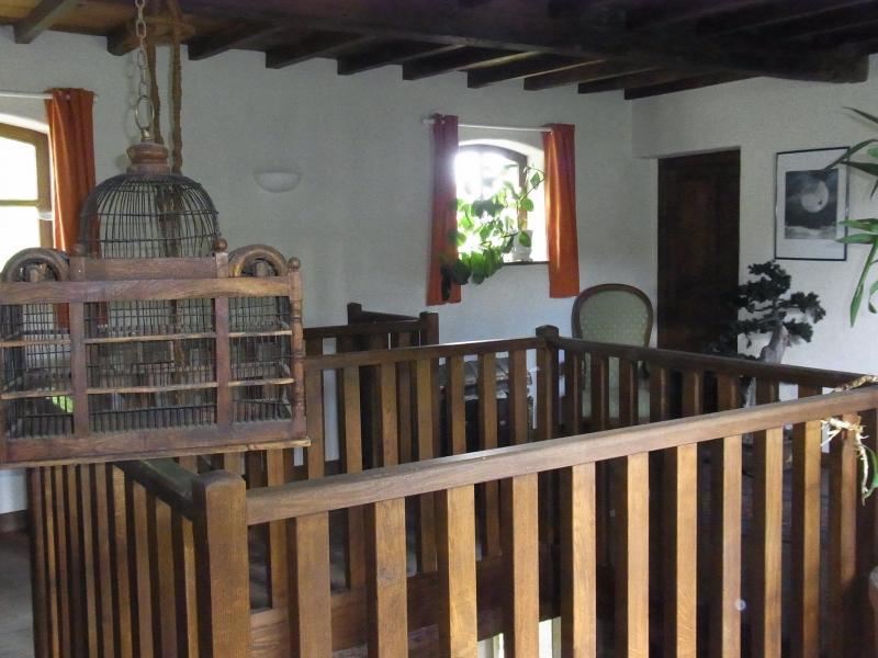 A l'étage, bibliothèque avec une corbeille en chêne. Une ancienne cage à oiseau complète la déco.