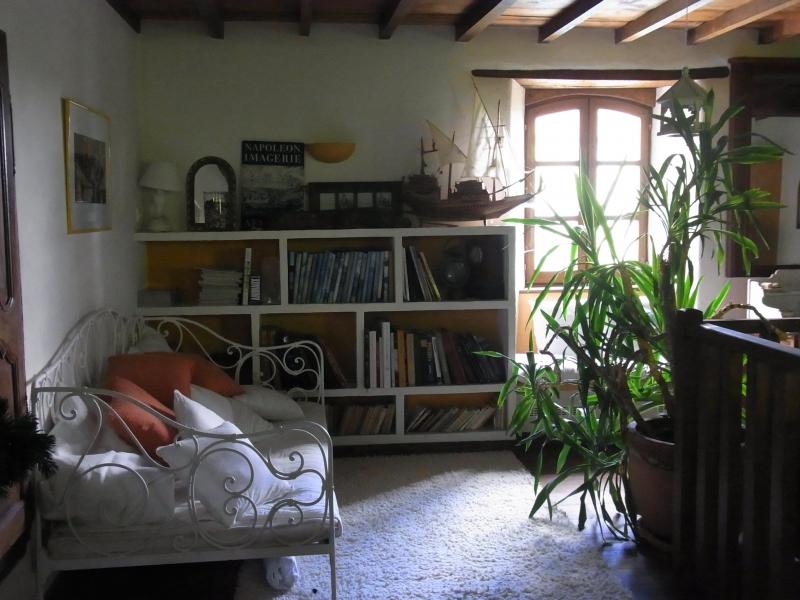 A l'étage, canapé en fer forgé ancien, bibliothèque avec des objets de décoration.