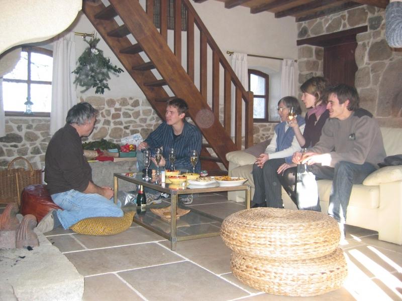 Au rez de chaussée, le salon équipé d'un canapé en cuir blanc en face d'une cheminée ancienne en pierre sur la gauche, avec ses chenêts en fonte.