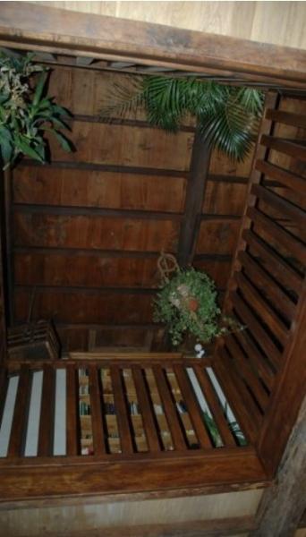 Contre plongée de la bibliothèque en haut avec son plafond en bois à la française. Hauteur de plafond 5 mètres. Escalier en chêne pour accéder à l'étage supérieur.