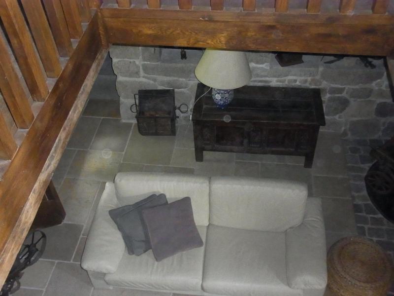 Vue sur le salon en bas à partir de la corbeille en chêne de la bibliothèque. Canapé en cuir blanc qui fait face à la cheminée ancienne. en pierre.