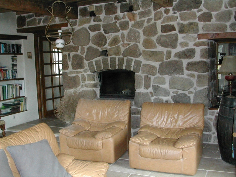Le salon de ma maison de campagne - Canapé 3 places et 2 fauteuils en cuir et vue sur le mur en pierres avec l'insert