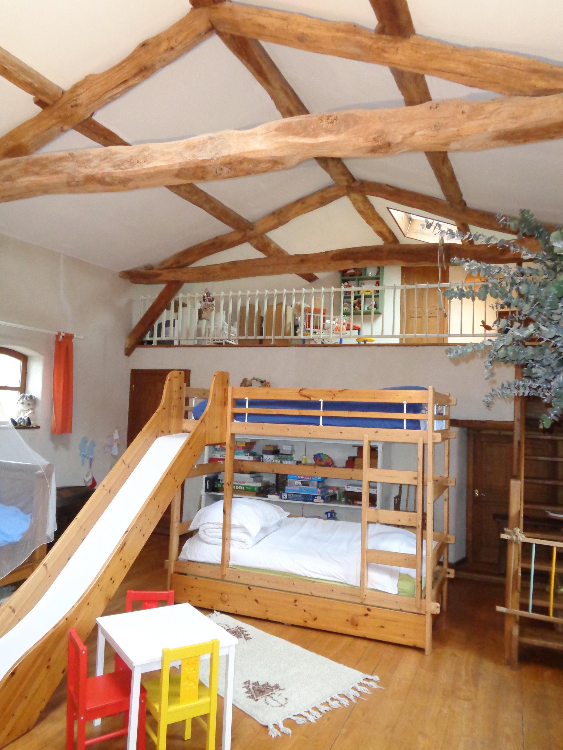 Lit à étage avec lit tiroir avec tobogan pour les petits. Ils vont adorer. A droite, table de jeu et l it enfant en fer forgé