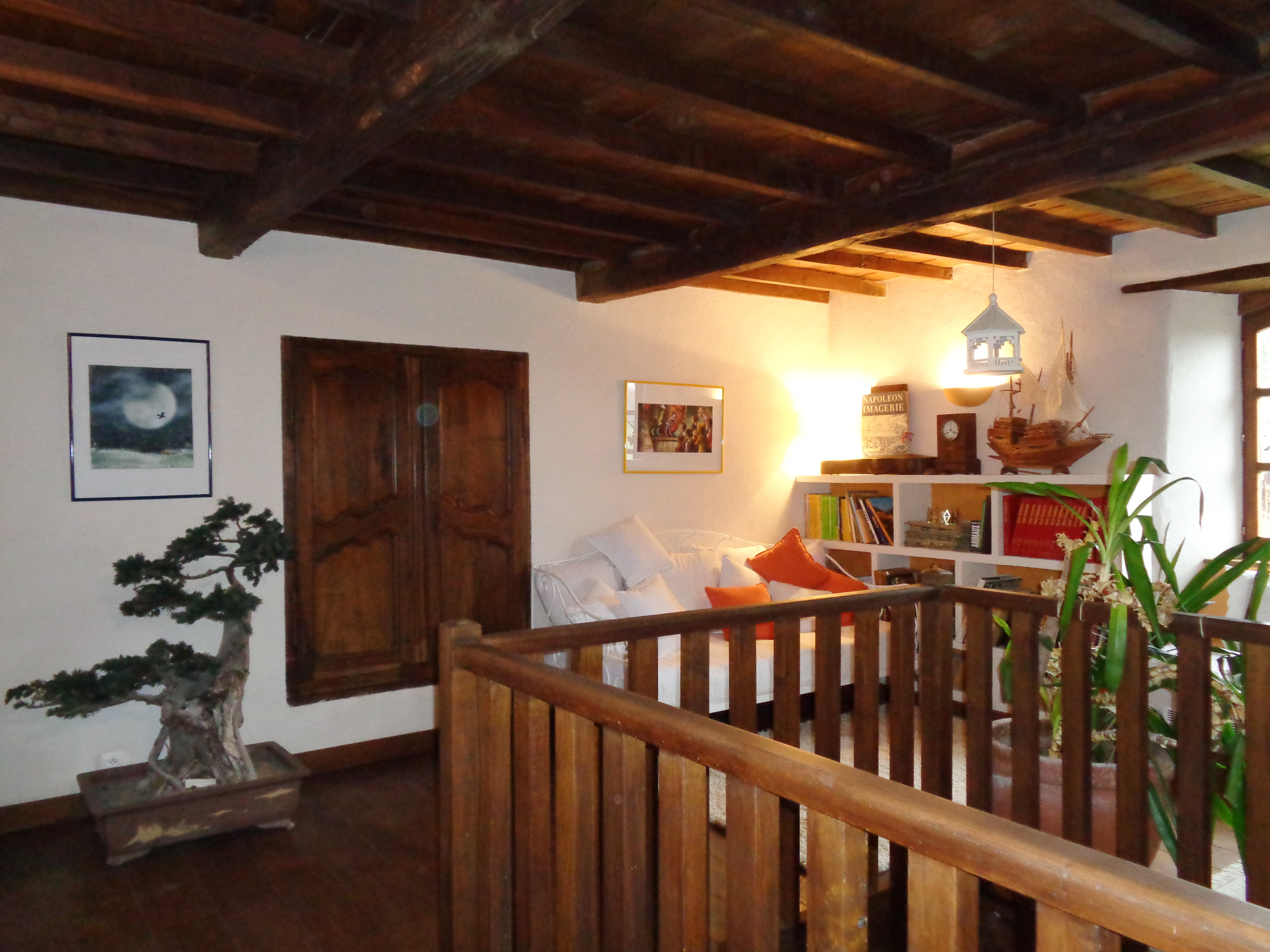 A l'étage, la pièce bibliothèque et sa rembarde de la corbeille en chêne avec vue sur le salon du bas et la cheminée en pierre d'époque.