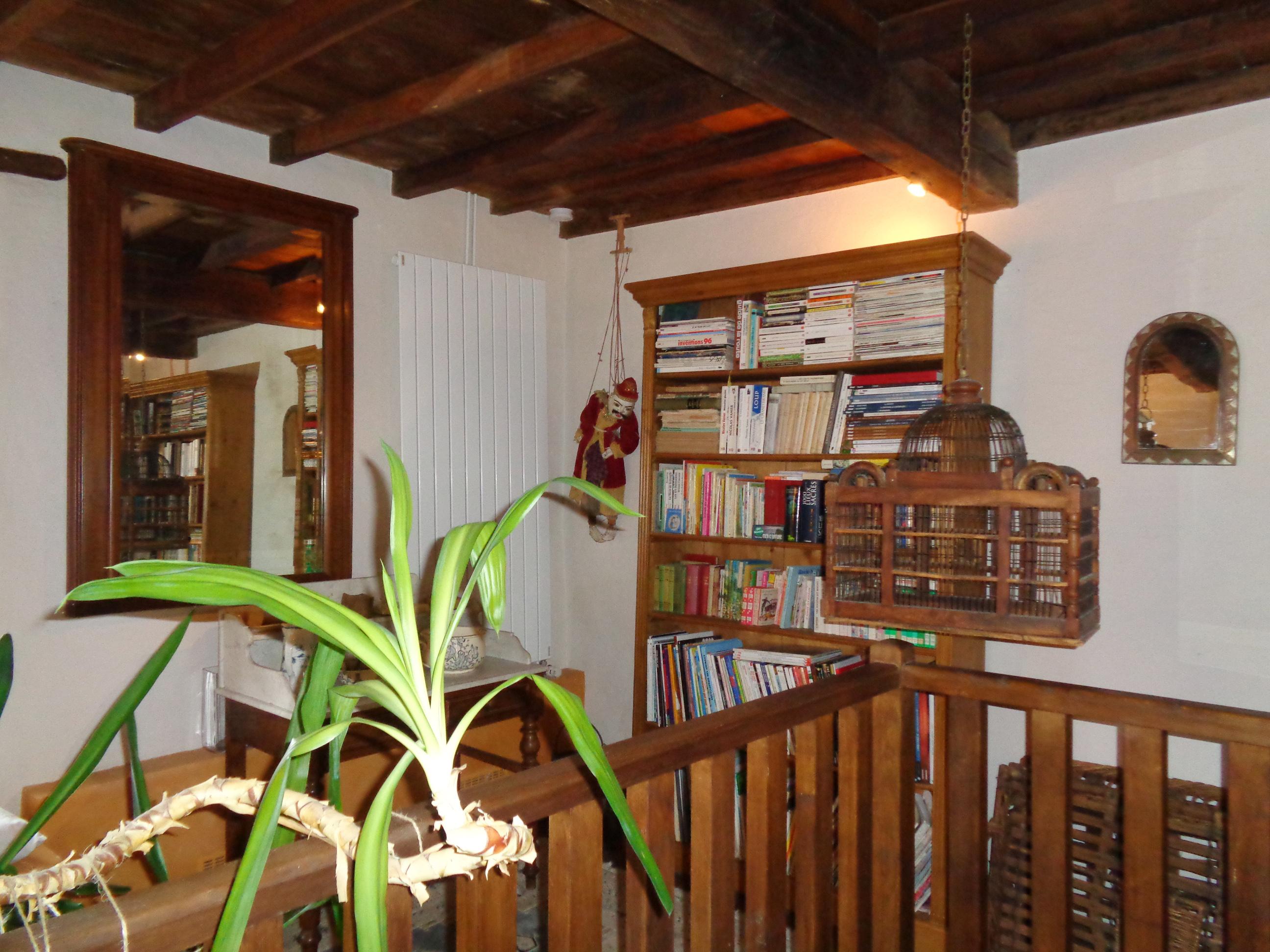Vue du salon du bas avec canapé en cuir blanc donnant sur une cheminée en pierres d'époque.