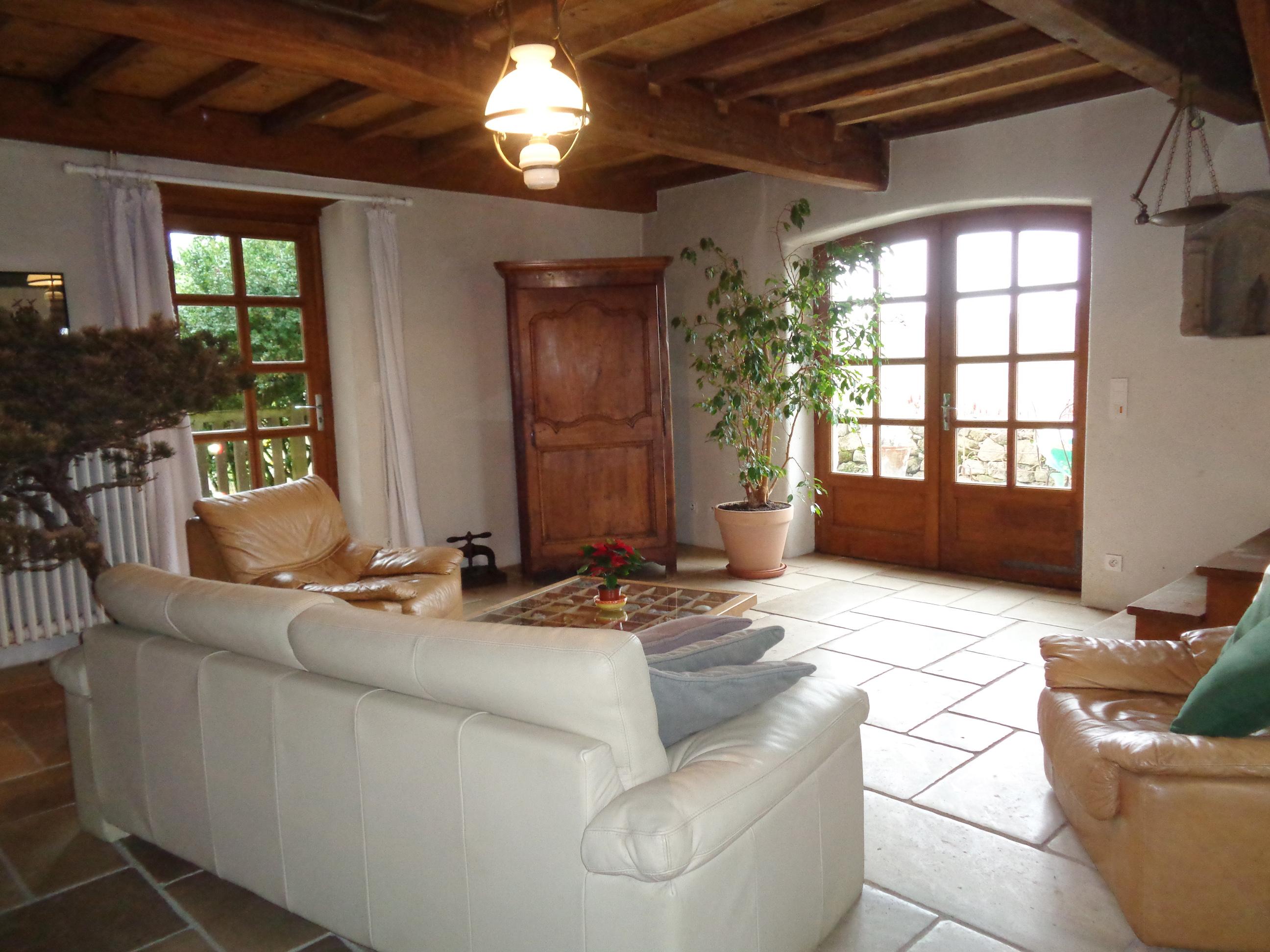 Le salon de ma maison de campagne - Canapé ancien et escalier en chêne menant aux chambres.
